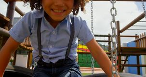 Front view of mixed-race schoolgirl playing on hanging tyre in the school playground 4k stock video