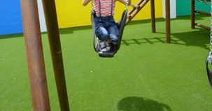 Front view of mixed-race schoolgirl playing on a swing at school playground 4k stock video