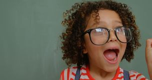 Front view of mixed-race schoolgirl with spectacle shouting in classroom at school 4k stock footage