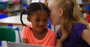 Front view of Mixed-race schoolgirls studying on laptop in the classroom 4k. Front view of Mixed-race schoolgirls studying on laptop in the classroom. They are stock video