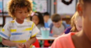 Front view of mixed-race schoolkids drawing on notebook in the classroom 4k. Front view of mixed-race schoolkids drawing on notebook in the classroom. They are stock footage