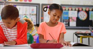 Front view of mixed-race schoolkids drawing on notebook in the classroom 4k. Front view of mixed-race schoolkids drawing on notebook in the classroom. They are stock video