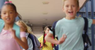 Front view of mixed-race schoolkids with schoolbags running in the corridor at school 4k