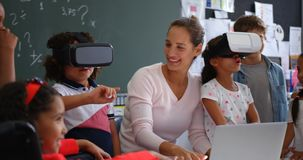 Front view of Mixed-race schoolkids using virtual reality headset with teacher and classmates i 4k. Front view of Mixed-race schoolkids using virtual reality stock video footage