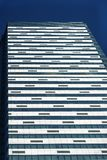 Front view of modern glass and concrete exterior of high rise building as abstract urban background, geometric pattern. Windows of high-rise tower royalty free stock images