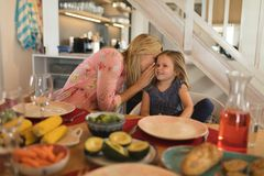 Mother whispering in daughter ear on dining table. Front view of a mother whispering in daughter ear on dining table at home stock photos