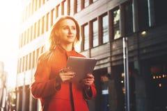 Front View Mujer atractiva joven en la capa anaranjada que se coloca en la calle de la ciudad que sostiene la tableta Estudiante imágenes de archivo libres de regalías
