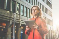 Front View Mujer atractiva joven en la capa anaranjada que se coloca en la calle de la ciudad que sostiene la tableta Estudiante fotografía de archivo libre de regalías