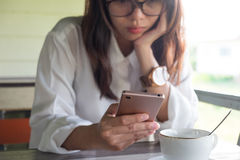 Front View Mujer que juega el teléfono móvil ella hace el wh serio de la cara Foto de archivo