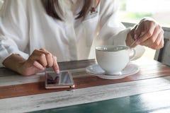Front View mujer que juega el teléfono móvil mientras que café del brebaje en mañana Imágenes de archivo libres de regalías