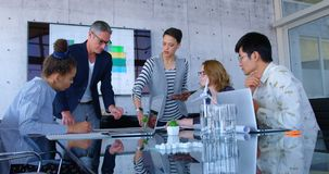 Multi-ethnic business people discussing over blueprint in the conference room at modern office 4 4k. Front view of multi-ethnic business people discussing over stock footage