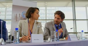 Business people sitting at the speaker table in seminar 4k. Front view of multi ethnic business people sitting at the speaker table while interacting with each stock footage