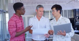 Multi-ethnic businessmen discussing over document in modern office 4k. Front view of multi-ethnic businessmen discussing over document in modern office. They are stock video