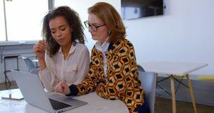 Multi-ethnic businesswomen using laptop in modern office 4k. Front view of multi-ethnic businesswomen using laptop in modern office. They are sitting at desk 4k stock video