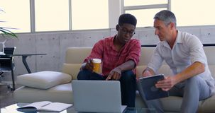 Multi-ethnic male executives discussing over laptop in modern office 4k stock video