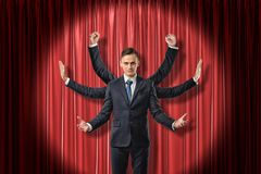 Front view of multiarmed businessman raising hands like Shiva, standing lit up by spotlight against red stage curtain. stock image