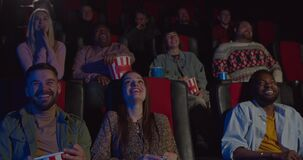 Front view of multiethnic spectators watching funny movie in cinema. People in cinema laughing from comedy film in movie