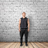 Front view of muscled young man looking up. On the background of white brick wall. Wellbeing. Muscleman. Workout and fitness Stock Photography