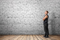 Front view of muscled young man looking up. On the background of white brick wall. Wellbeing. Muscleman. Workout and fitness Stock Images