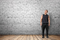 Front view of muscled young man looking up. On the background of white brick wall. Wellbeing. Muscleman. Workout and fitness Royalty Free Stock Images