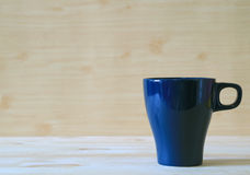Front view of navy blue mug on the light color wooden table Stock Photos