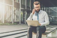 Front View O homem de negócios novo na camisa branca senta-se no parque no banco, jogando seu laço sobre seu ombro, trabalhando s foto de stock