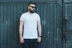 Front View O homem farpado novo do moderno vestido no t-shirt e nos óculos de sol brancos é suportes contra a parede de madeira e Imagens de Stock Royalty Free