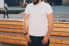 Front View O homem farpado novo do moderno vestido no t-shirt e nos óculos de sol brancos é suportes na rua da cidade Zombaria ac imagens de stock