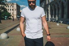 Front View O homem milenar farpado novo vestido no t-shirt e nos óculos de sol brancos é suportes na rua da cidade Zombaria acima Fotografia de Stock Royalty Free