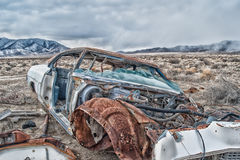 Front view of an old abandoned car and parts in the desert Stock Photography