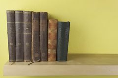 Front view of old books stacked on a shelf. Stock Photos