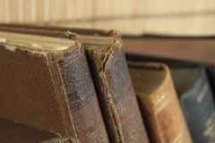 Front view of old books stacked on a shelf. Stock Images