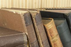Front view of old books stacked on a shelf. Royalty Free Stock Photos