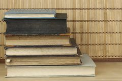 Front view of old books stacked on a shelf. Stock Photo