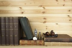 Front view of old books stacked on a shelf. Royalty Free Stock Images