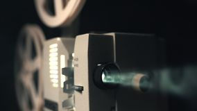 Front view of an old-fashioned antique Super 8mm film projector, projecting a beam of light in a dark room next to a royalty free stock photo