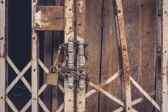 The front view old gold steel lock and damaged and rusted steel door on wooden door stock photography