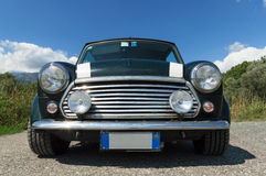 Front view of an old Mini Cooper. Front view of a green Mini Cooper with a blue sky Royalty Free Stock Photography