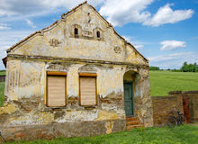 Front view of an old, traditional house in a field of wheat Royalty Free Stock Image