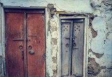 A front view of old vintage wood carved closed doors of an old house with cracked wall in streets of Lohara village in Ludhiana, P royalty free stock image
