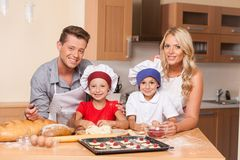 Front view of parents cooking together with children. Stock Image