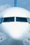 Front view of passenger airplane. Front view of white passenger airplane with ground equipment reflected in the hull Stock Image