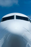 Front view of passenger airplane. Front view of white passenger airplane with ground equipment reflected in the hull Royalty Free Stock Images