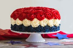 Front View of Patriotic Cake in Red White and Blue Rosettes. Front view of patriotic cake in red, white and blue on white stand surrounded by stars Stock Photos