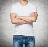 Front view of a person in a white V shape t-shirt with crossed hands. Royalty Free Stock Images