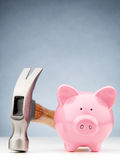 Front View of a Piggy Bank and Hammer Stock Photo
