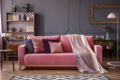 Front view of a pink sofa with pillows and blanket, vintage cupb. Oard in the background in a glamorous living room interior Royalty Free Stock Images