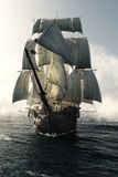 Front view of a pirate ship vessel piercing through the fog headed toward the camera . Royalty Free Stock Image