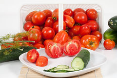 Front View of Plated Tomatoes and Cucumber. An front detail studio view of plated sliced tomatoes and cucumber with a basket of ripe field tomatoes and a sprig Stock Photos