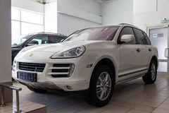 Front view of Porsche Cayenne 957 2007 in white color after cleaning before sale in a sunny day on dealership parking royalty free stock photography